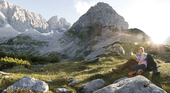 Austria, Tyrol, mother and daughter reading book in mountainscape at sunset - FKF03287