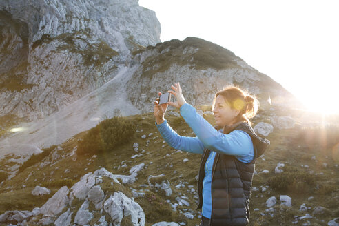 Austria, Tyrol, woman taking cell phone picture in mountainscape at sunset - FKF03296