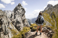 Austria, Tyrol, woman on a hiking trip in the mountains looking at view - FKF03299