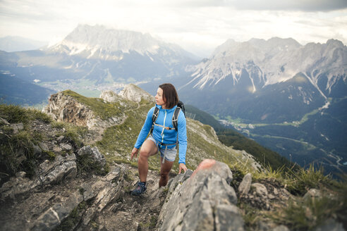 Austria, Tyrol, woman on a hiking trip in the mountains looking around - FKF03326