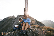 Austria, Tyrol, mother and son on a hiking trip with book at the summit - FKF03329
