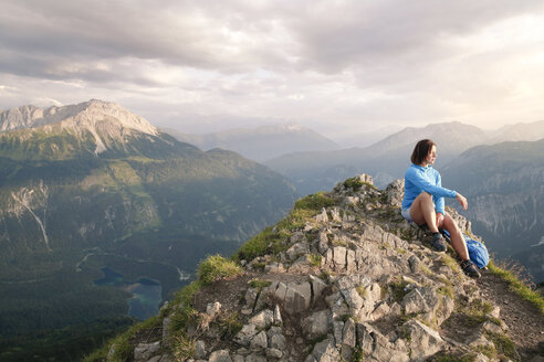 Austria, Tyrol, woman on a hiking trip in the mountains sitting on peak - FKF03332