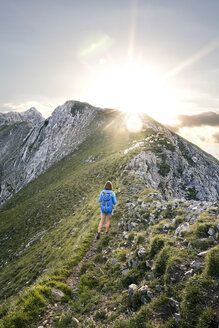 Austria, Tyrol, woman on a hiking trip in the mountains at sunset - FKF03335