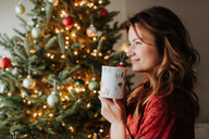 Woman drinking coffee beside decorated Christmas tree - ISF20786