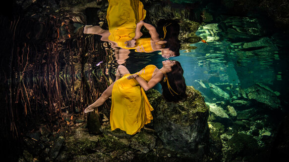 Woman in yellow gown floating underwater, Cenote, Quintana Roo, Mexico - ISF20792