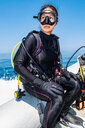 Woman in scuba gear on the way to a dive site,  Komodo Island, East Nusa Tenggara, Indonesia - ISF20810