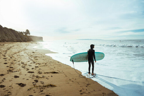 Surfer with surfboard on beach, Morro Bay, California, United States - ISF20846