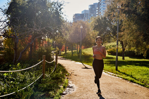 Woman jogging in city park, Barcelona, Catalonia, Spain - ISF20867