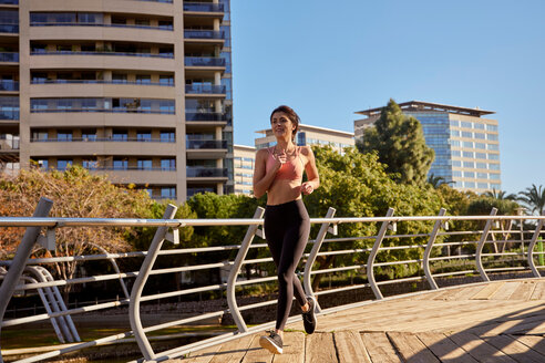 Woman jogging in city park, Barcelona, Catalonia, Spain - ISF20870