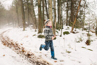 Boy running in snow landscape through forest - ISF20876