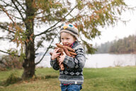 Boy with armful of brown pine cones, Kingston, Ontario, Canada - ISF20879