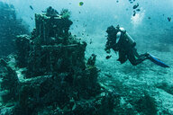 Scuba diver checking out artificial reef off coast, Tulamben, Bali, Indonesia - ISF20888