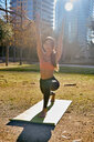Woman practising yoga in city park, Barcelona, Catalonia, Spain - ISF20894