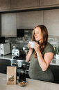 Pregnant woman brewing herbal tea with french press - ISF20909