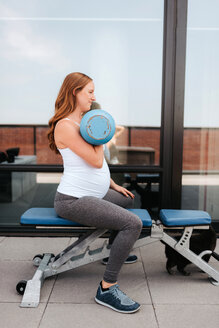 Pregnant woman using weights on balcony - ISF20915