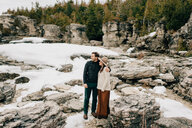 Couple standing on snow and rock landscape, Tobermory, Canada - ISF20945