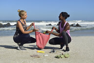 Two women cleaning the beach from plastic waste - ECPF00429