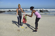 Two women cleaning the beach from plastic waste - ECPF00432