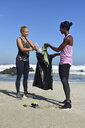 Two women cleaning the beach from plastic waste - ECPF00435