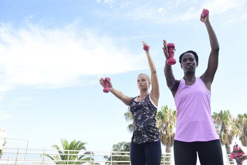 Two women doing fitness exercises with dumbbells outdoors - ECPF00471