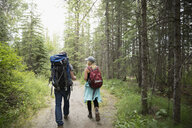 Couple with backpacks backpacking, hiking on trail in woods among trees - HEROF21052