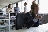 Businessman reviewing paperwork at office desk - HEROF21115