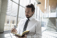 Businessman writing in journal in office lobby - HEROF21151