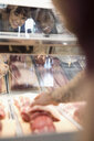 Butcher reaching for raw red meat in display case for smiling female customers - HEROF21217