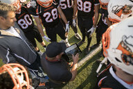 Coach with digital tablet showing video to teenage boy high school football team in huddle on football field - HEROF21223