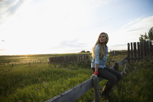 Pensive young blonde female farmer sitting on fence and looking away on farm - HEROF21260