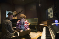 Pianists playing grand piano, writing music at laptop in recording studio - HEROF21380