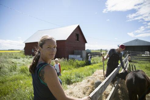 Portrait smiling female farmer at fence on sunny farm - HEROF21428