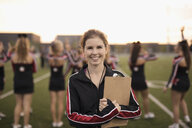 Portrait smiling, confident high school cheerleading coach with clipboard on sideline of football field - HEROF21491