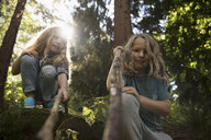 Portrait girl sisters playing with sticks in woods - HEROF21515