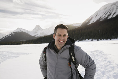 Smiling man in snowy field below mountains - HEROF21533