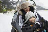Smiling mother and daughter riding in dogsled - HEROF21536