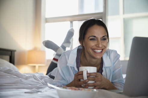 Smiling woman with coffee and laptop on bed - HEROF21626