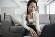 Woman using laptop in living room - HEROF21641