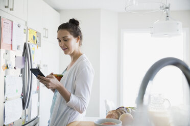 Woman in pajamas drinking morning coffee and texting - HEROF21647