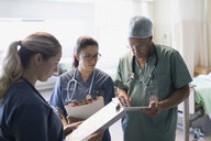 Surgeon doctor and nurses with digital tablet discussing medical record in hospital - HEROF21737