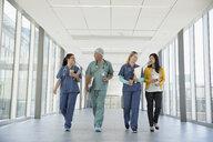 Surgeon, doctor and nurses talking and walking in hospital corridor - HEROF21749