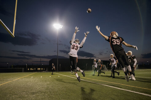 Teenage boy high school football player receiver jumping to catch the ball on football field - HEROF21791