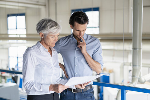Businessman and senior businesswoman looking at plan in a factory - DIGF05729
