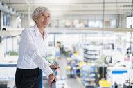 Senior businesswoman on upper floor in factory overlooking shop floor - DIGF05735