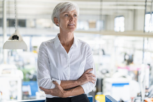 Portrait of senior businesswoman in a factory looking around - DIGF05738
