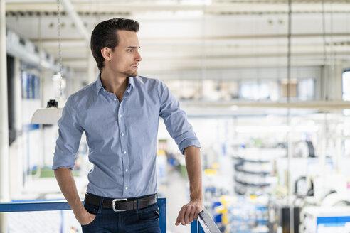 Businessman on upper floor in factory overlooking shop floor - DIGF05741