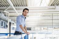 Businessman on upper floor in factory overlooking shop floor - DIGF05744