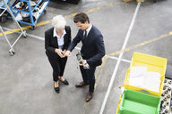 Businessman and senior businesswoman examining workpiece in a factory - DIGF05747