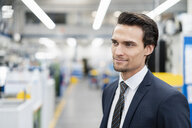 Portrait of confident businessman in a factory looking around - DIGF05753