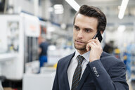 Portrait of businessman on cell phone in a factory - DIGF05756